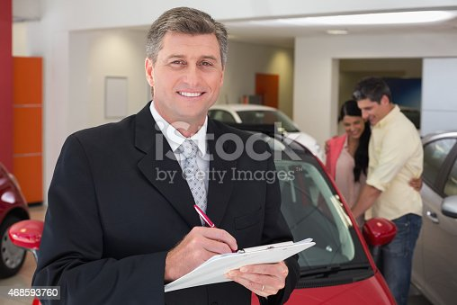 1138561232 istock photo Smiling businessman writing on clipboard 468593760