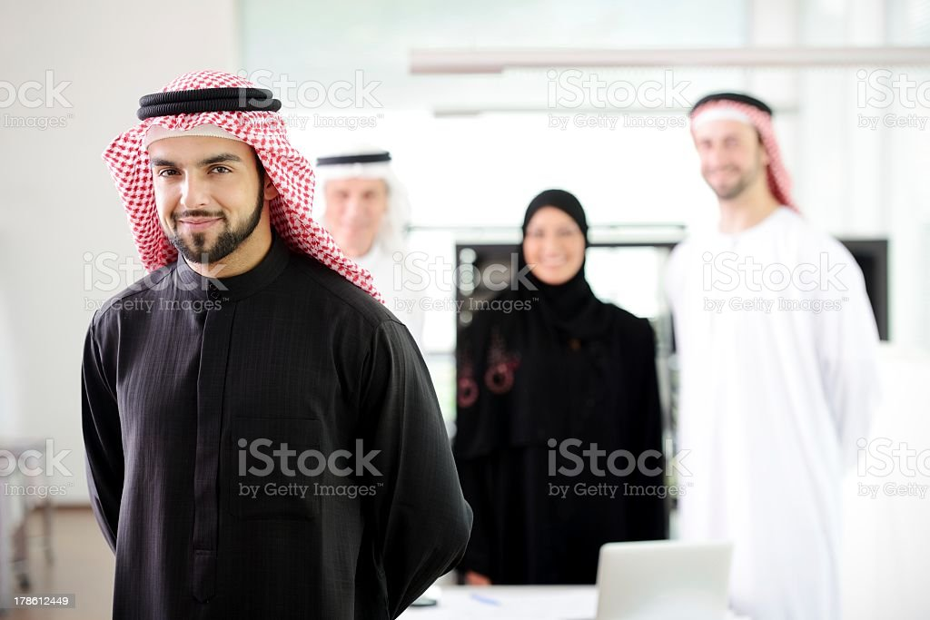 Smiling businessmen and woman in Arabian gear stock photo