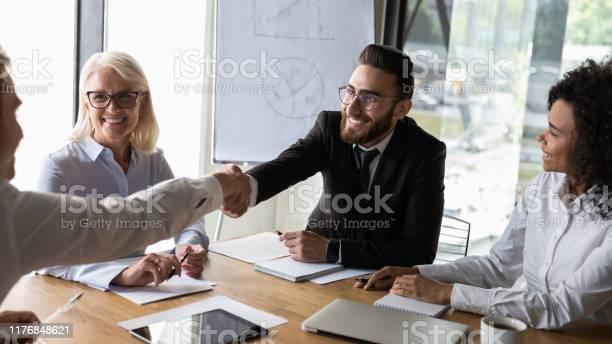 Smiling businessmen handshaking at business briefing making agreement picture id1176848621?b=1&k=6&m=1176848621&s=612x612&h=cmme nny qpg6zbivsidlnwqpgmsnhqaemmkrt7jnge=