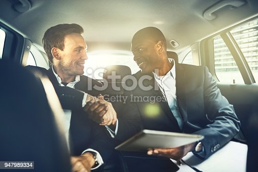 istock Smiling businessmen shaking hands in the backseat of a car 947989334