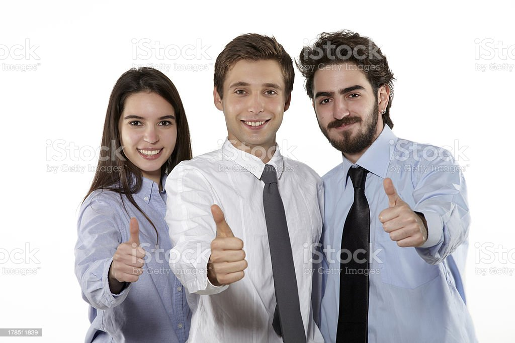 Smiling businessteam giving you thumbs up royalty-free stock photo