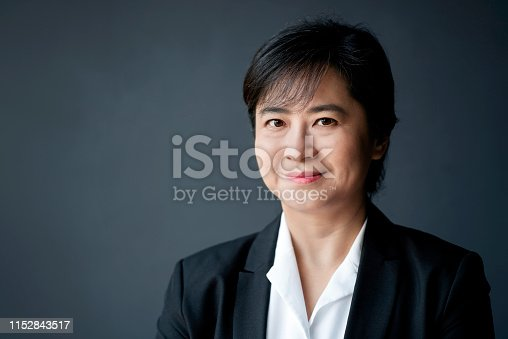 Smiling businesswoman against gray background. Portrait of white collar worker is wearing suit. She is with confident look on her face.
