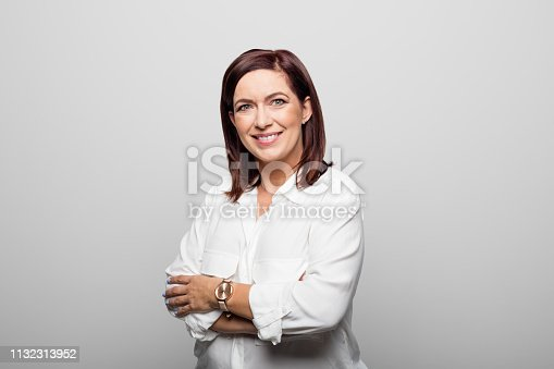 1132314350 istock photo Smiling businesswoman against white background 1132313952