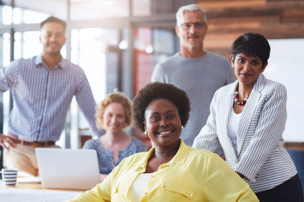 Smiling businesswoman and her team working in an office stock photo