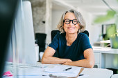Portrait of confident mature businesswoman. Smiling female professional is working in creative office. She is wearing eyeglasses.