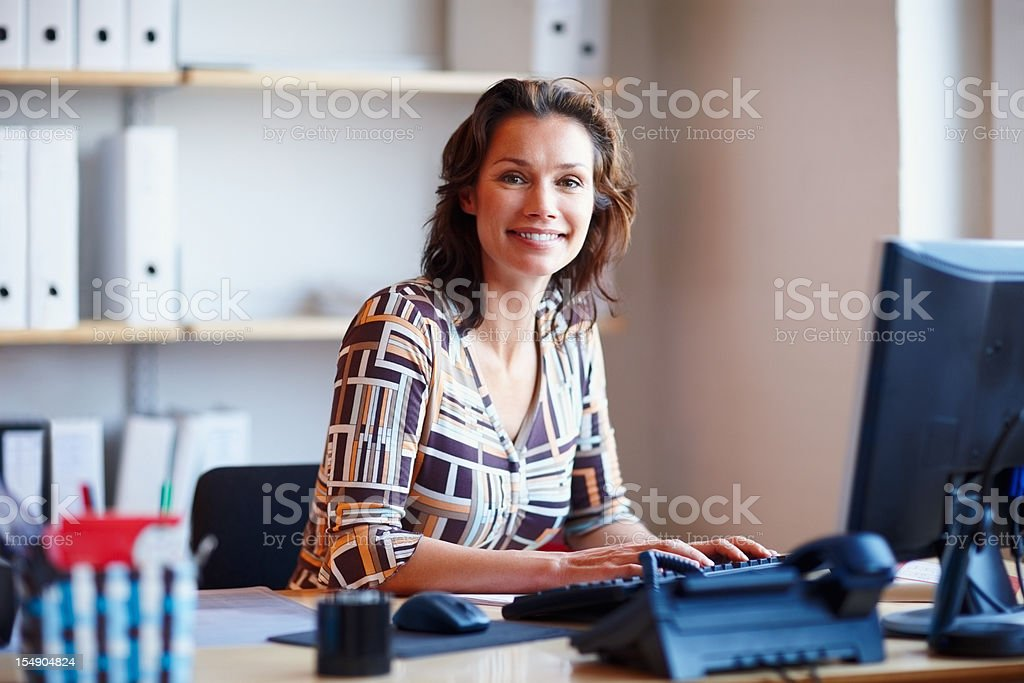 Smiling businesswoman at office desk with a computer stock photo