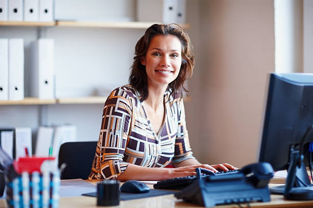 Smiling businesswoman at office desk with a computer Portrait of a smiling mature businesswoman at office desk with a computer administrator stock pictures, royalty-free photos & images