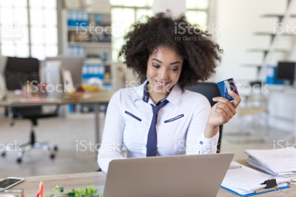 Smiling businesswoman at office shopping with credit card stock photo