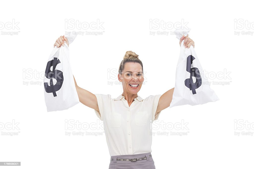 Smiling businesswoman carrying money bags royalty-free stock photo