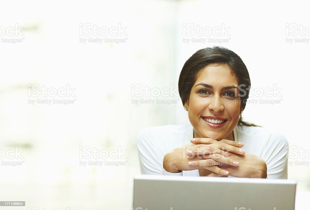 Smiling businesswoman clasping hands behind laptop royalty-free stock photo