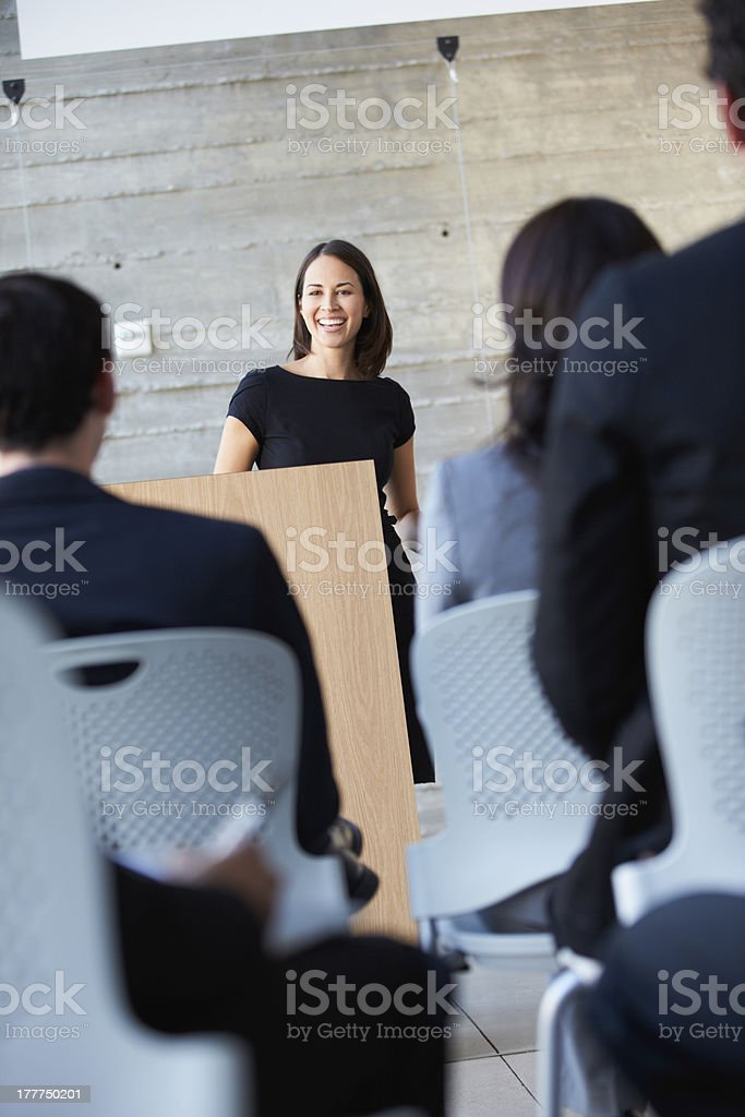 Smiling businesswoman delivers a presentation to an audience stock photo