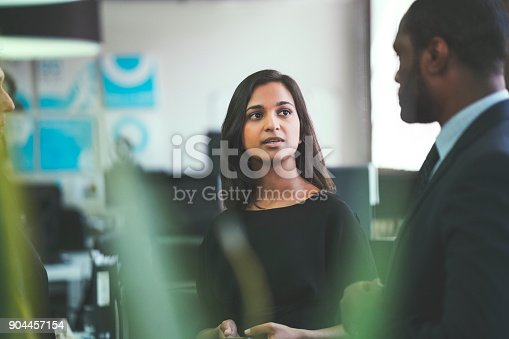 istock Smiling businesswoman discussing with coworkers 904457154