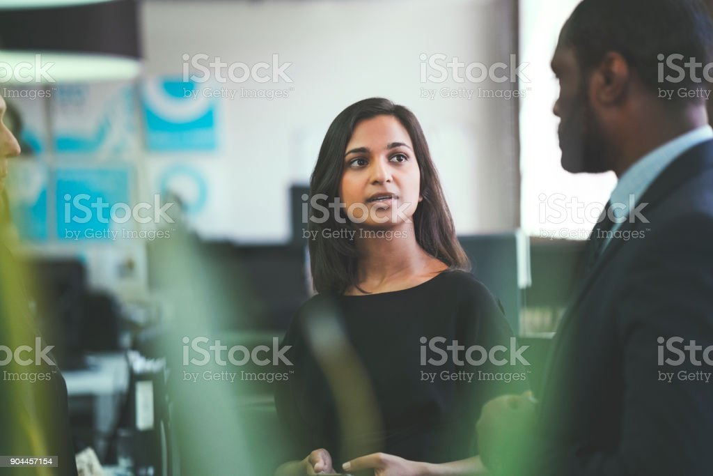 Smiling businesswoman discussing with coworkers stock photo