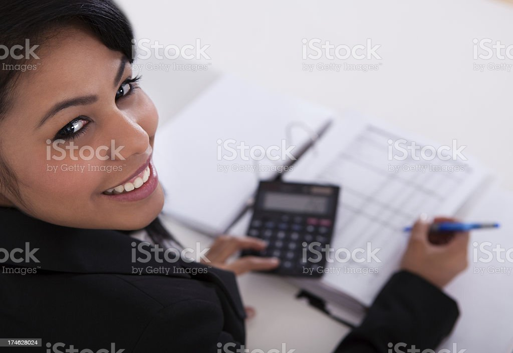 Smiling businesswoman doing calculations at a table stock photo