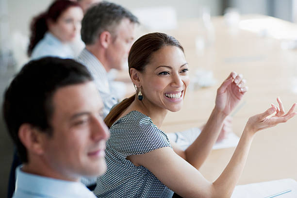 Smiling businesswoman gesturing in meeting in conference room  persuasion stock pictures, royalty-free photos & images