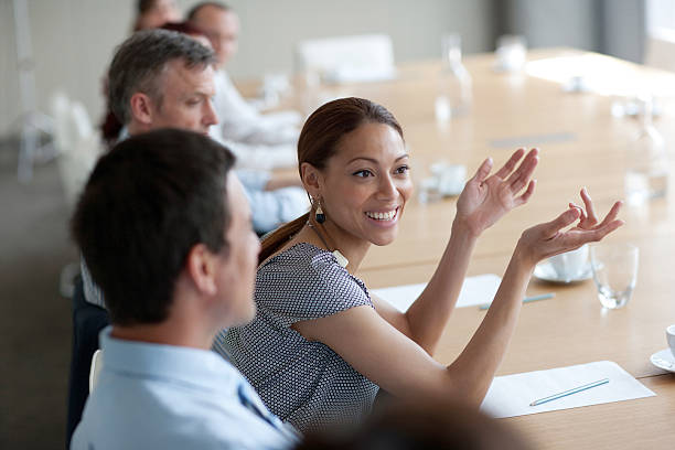 Smiling businesswoman gesturing in meeting in conference room stock photo