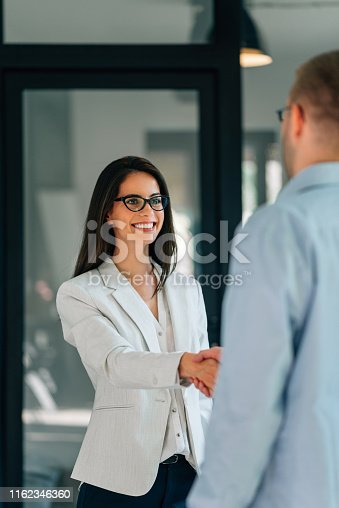 Smiling businesswoman handshake with businessman while standing in the office.