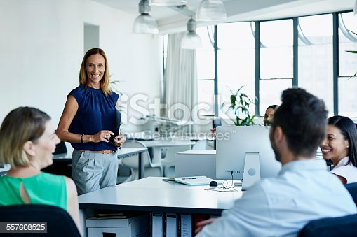557608497istockphoto Smiling businesswoman having discussion with team 557608525