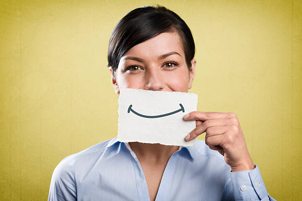 Smiling businesswoman holding blank white card in front of mouth. stock photo