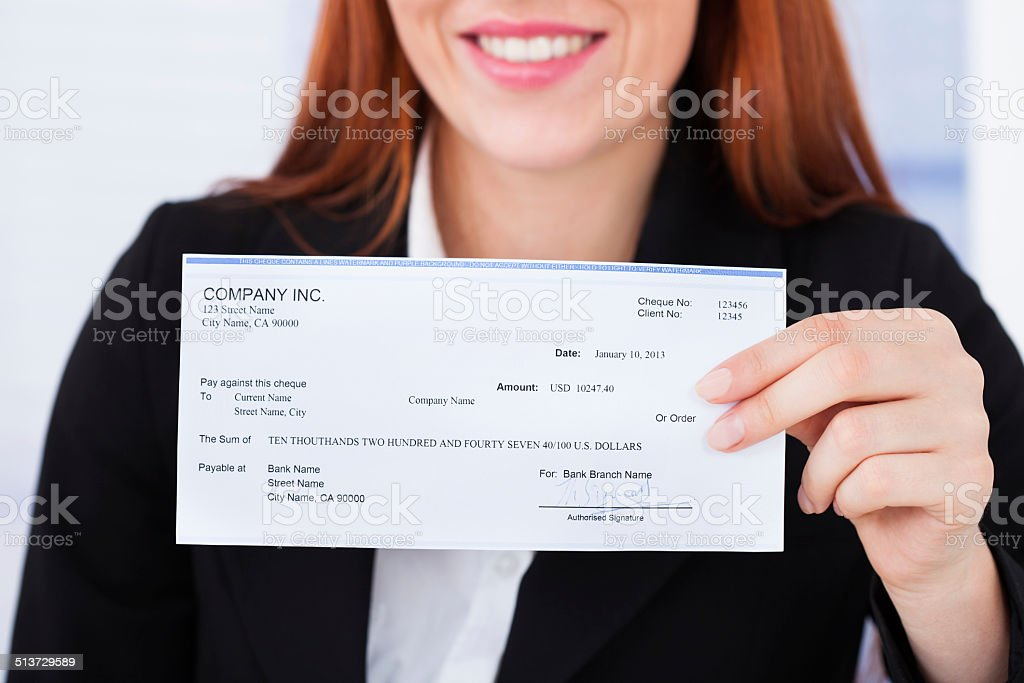 Smiling Businesswoman Holding Cheque stock photo