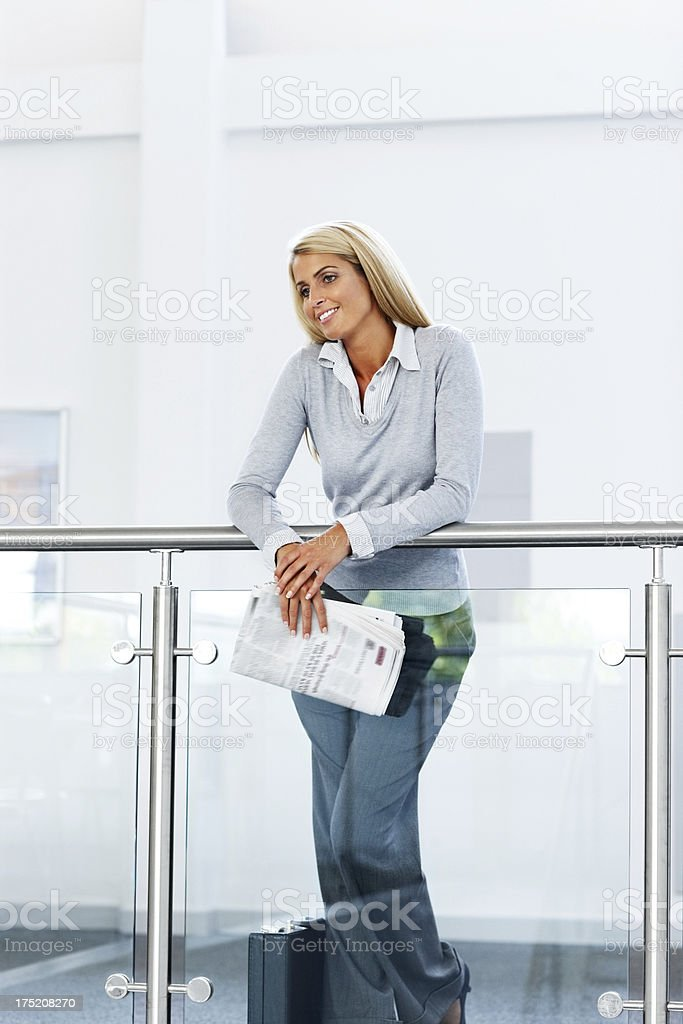Smiling businesswoman holding newspaper by a railing royalty-free stock photo