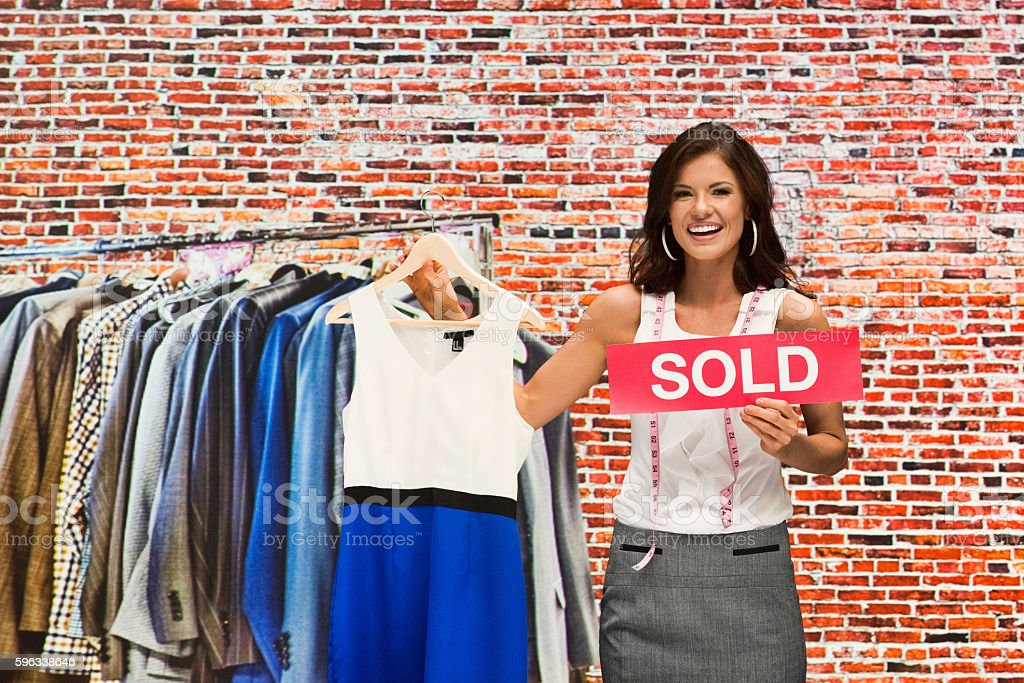 Smiling businesswoman holding sold sign royalty-free stock photo