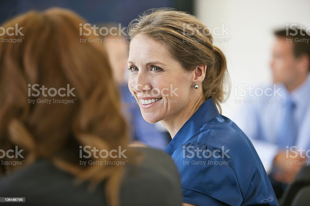 Smiling businesswoman in a meeting in conference room at office royalty-free stock photo