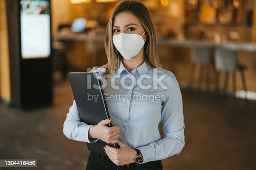 Portrait of one young businesswoman, restaurant manager or owner with protective face mask standing and holding laptop in cafe, looking at camera and smiling behind the mask