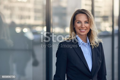 981750034istockphoto Smiling businesswoman in front of a glass window 655856700