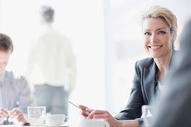 smiling businesswoman in meeting - four lawyers stockfoto's en -beelden