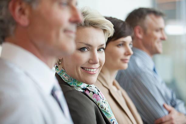 smiling businesswoman in row of business people - four lawyers stockfoto's en -beelden