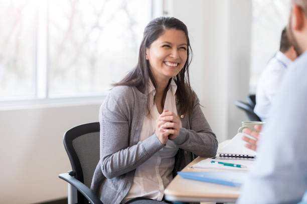 Smiling businesswoman interviews job candidate Confident mid adult businesswoman smiles while talking with a job candidate during a job interview. filipino ethnicity stock pictures, royalty-free photos & images