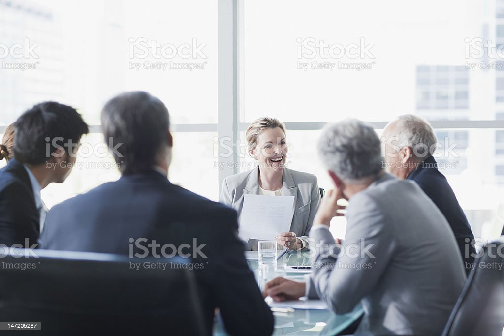 Smiling businesswoman leading meeting in conference room stock photo