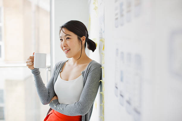 smiling businesswoman leaning against whiteboard and drinking coffee - 休息中 個照片及圖片檔