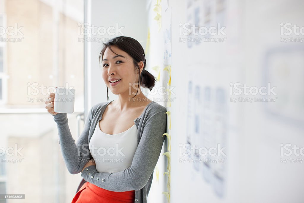 Smiling businesswoman leaning against whiteboard and drinking coffee stock photo