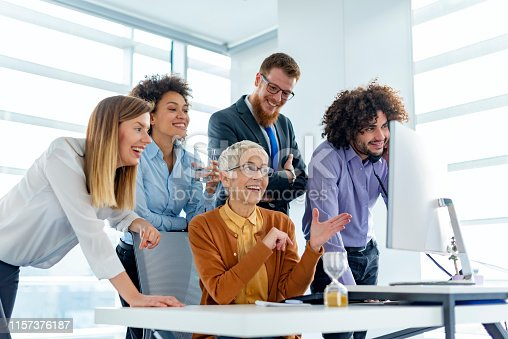 956725740istockphoto Smiling businesswoman listening to colleagues at a meeting 1157376187