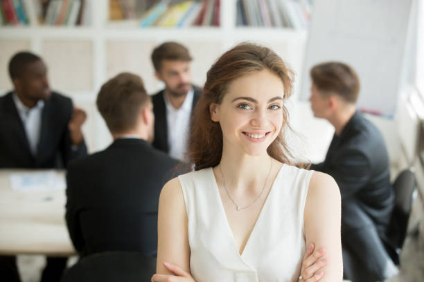 Femme souriante regardant la caméra, réunion à fond, de l'équipe portrait - Photo