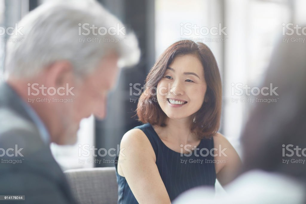 Smiling businesswoman looking at colleague stock photo
