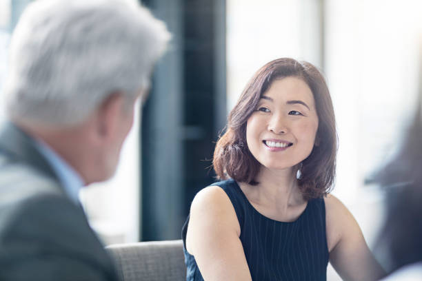 Smiling businesswoman looking at mature coworker stock photo