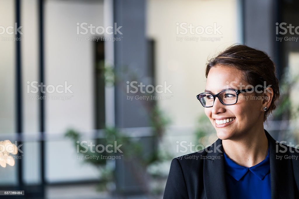 Smiling businesswoman looking away in office stock photo