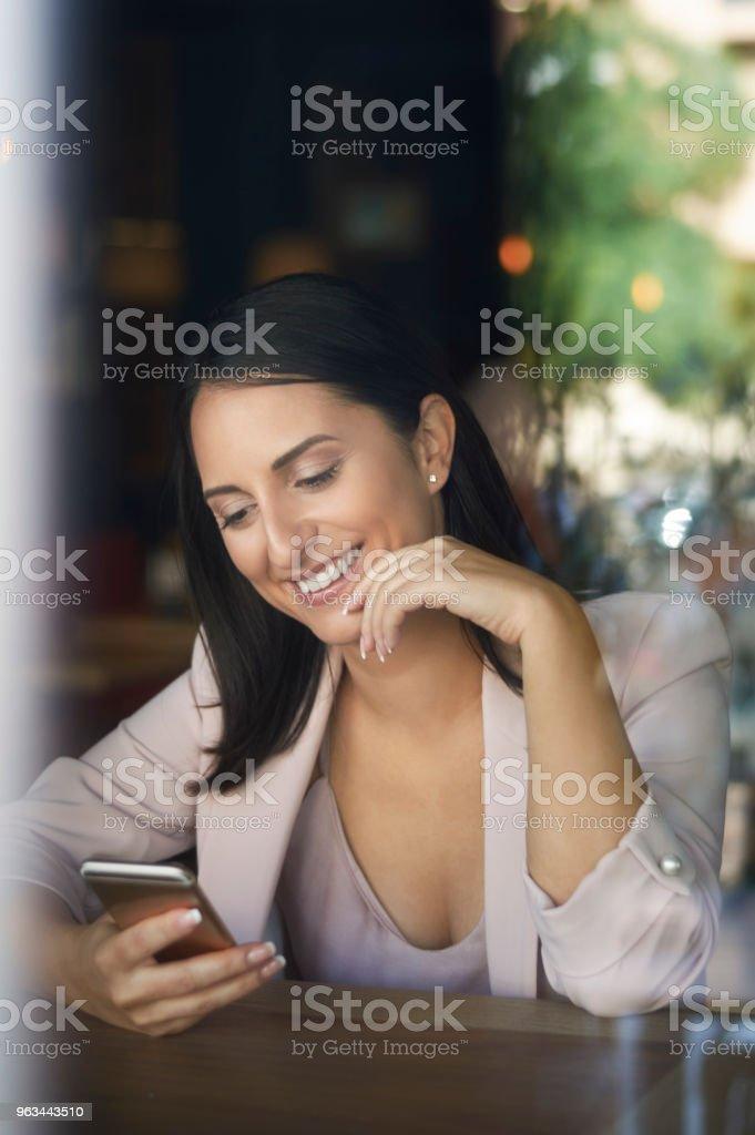 Cep telefonu kafe penceresinde bakarak gülümseyen iş kadını - Royalty-free Ayrışık odak Stok görsel