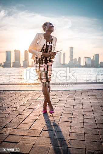 Shot of African-American thoughtful businesswoman on the go holding digital tablet and smiling in New York City, USA. Skyscrapers and blue sky in the back.