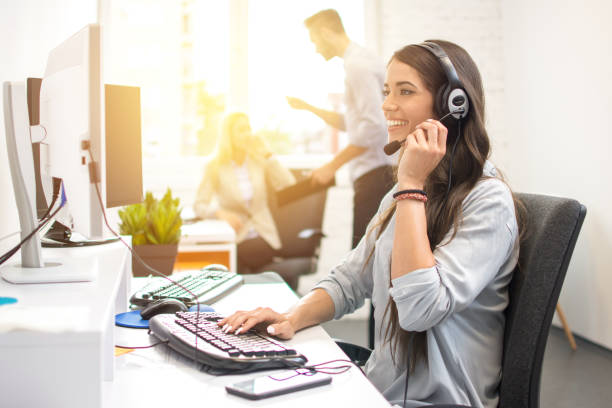 Smiling businesswoman or helpline operator with headset using computer at office stock photo