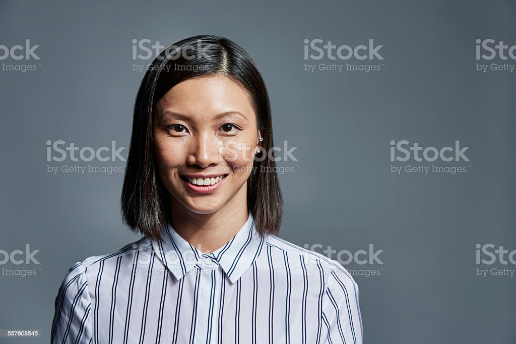 Smiling businesswoman over gray background Portrait of smiling young businesswoman over gray background 2015 Stock Photo