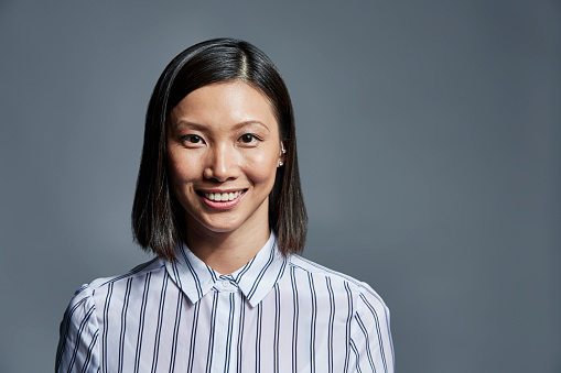 Portrait of smiling young businesswoman over gray background