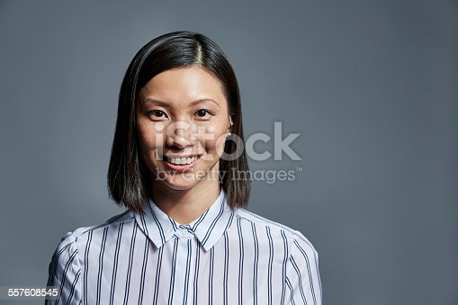 istock Smiling businesswoman over gray background 557608545
