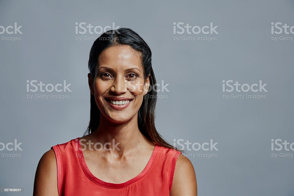 Smiling businesswoman over gray background stock photo