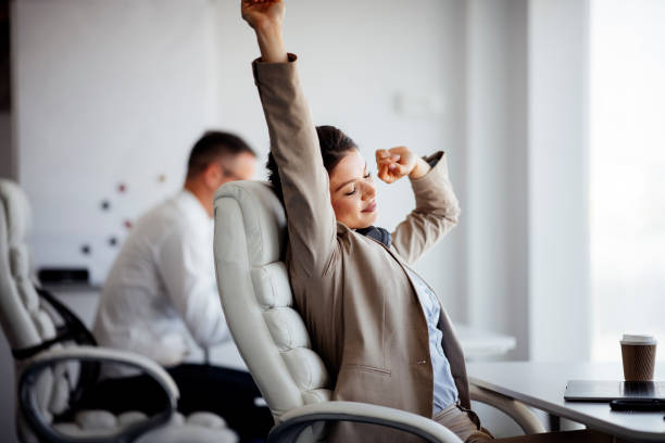 Smiling businesswoman relaxing leaning back in office chair stock photo stock photo