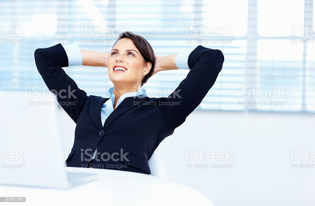 Smiling businesswoman relaxing with hands behind head in office royalty-free stock photo