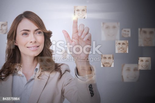 Smiling businesswoman selecting digital interface showing young woman